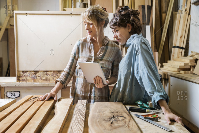 Two women looking at a tablet in a woodworking shop