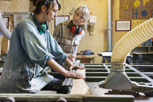 Two women using a saw in a woodworking shop