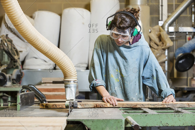 Young woman using a power saw to cut a board in a woodworking shop