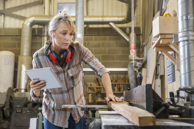 Woman using a tablet while working in a woodworking shop