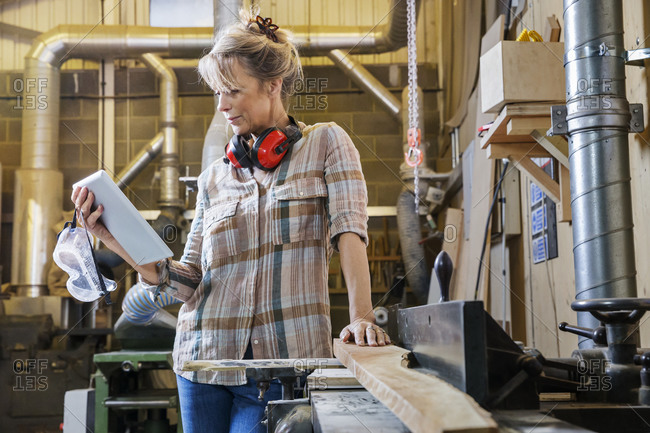 Woman reading a tablet while working in a woodworking shop