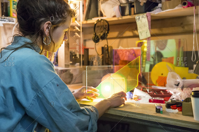 Young woman in a shop working with a sheet of colored plastic
