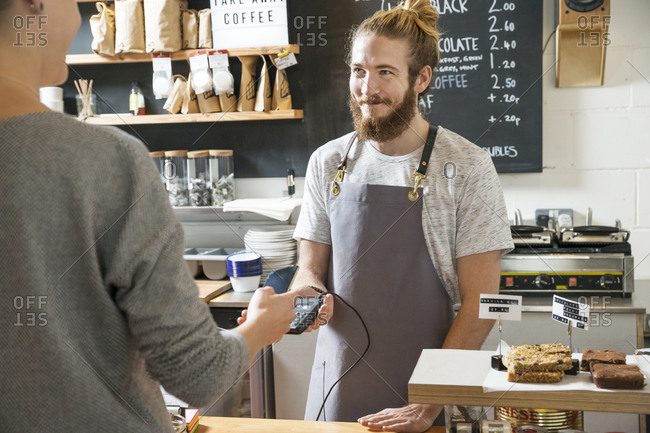 Young man working in a coffee shop accepting a customer's payment