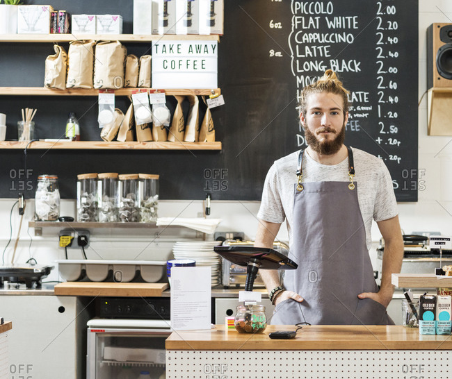 Young man standing behind the bar at a coffee shop