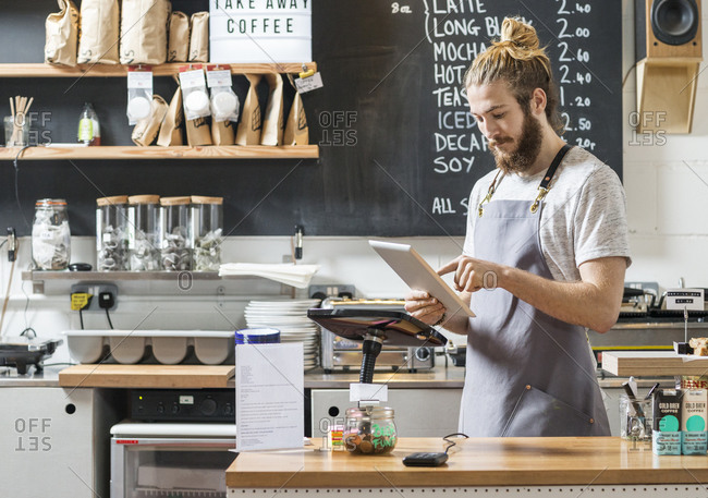 Young man working at a coffee shop using a tablet