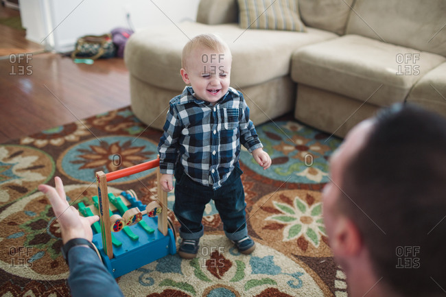 Toddler boy standing beside a toy laughing at his father