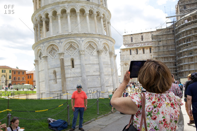 Pisa, Italy - May 27, 2015: Tourists taking photos in front of the Leaning Tower of Pisa