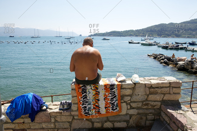 Man sitting on a ledge by the water