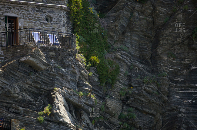 Two deck chairs of a deck built into a cliff