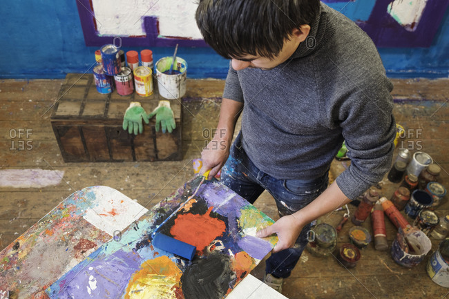 Male artist rolling paint onto a canvas