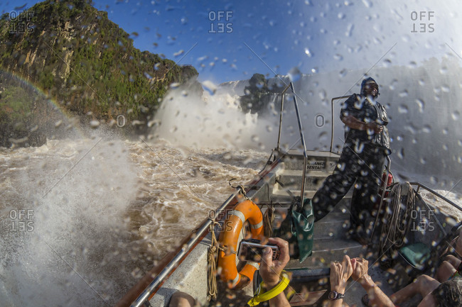 Misiones, Argentina - October 18, 2015: Tourists take a river boat to the base of the falls, Iguazu Falls National Park, UNESCO World Heritage Site, Misiones, Argentina