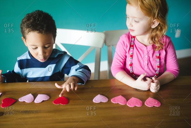 Two children making a Valentine\'s Day craft