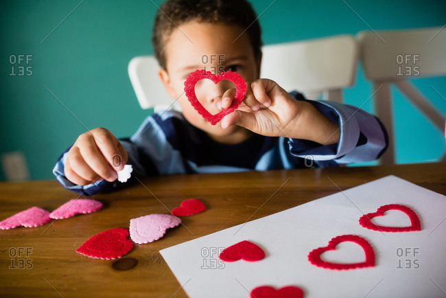 Little boy holding heart while making a Valentine\'s Day craft