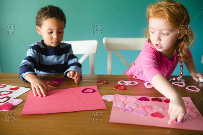 Two kids making a Valentine\'s Day craft