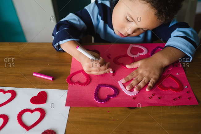 Little boy drawing on a Valentine\'s Day craft