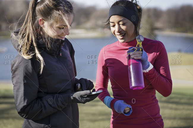 Two women in workout gear looking at smartphone together