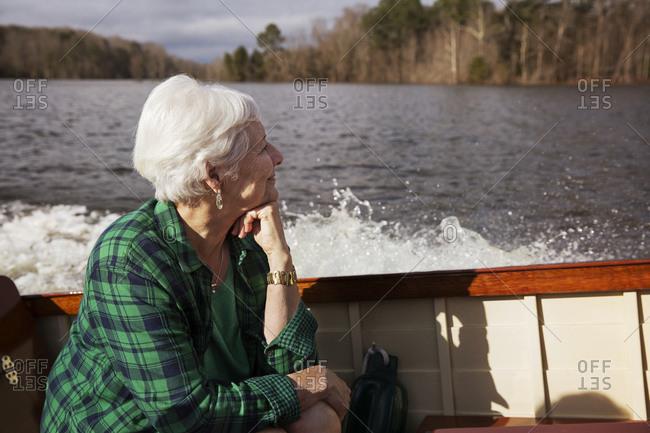 Senior woman enjoying boat ride in autumn