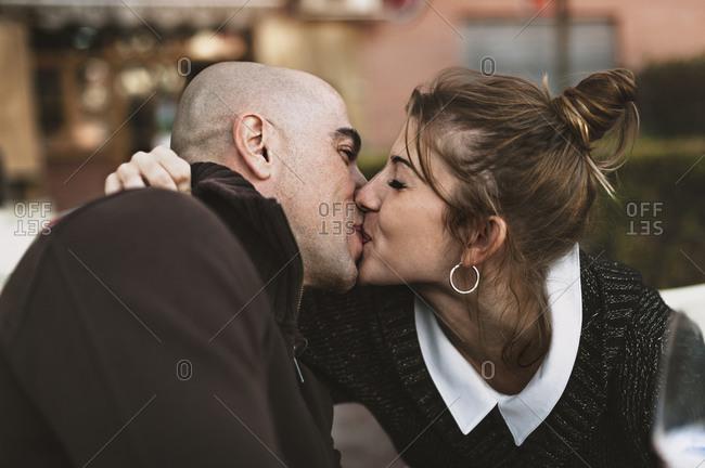 Man and woman kiss at outdoor café