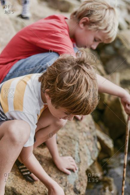 Two young boys exploring rock pools at coast
