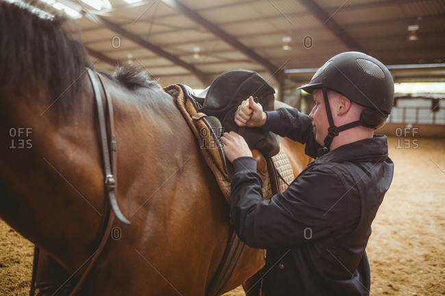 Female rider securing saddle in the countryside