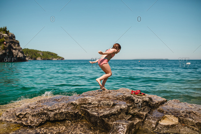 Girl about to dive into the ocean from rocks