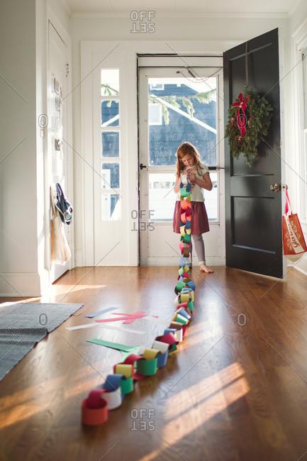 Little girl assembling a paper streamer
