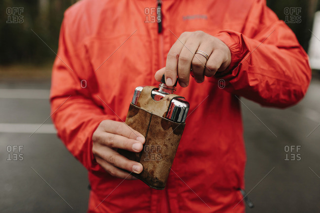 Man in rain coat holding flask