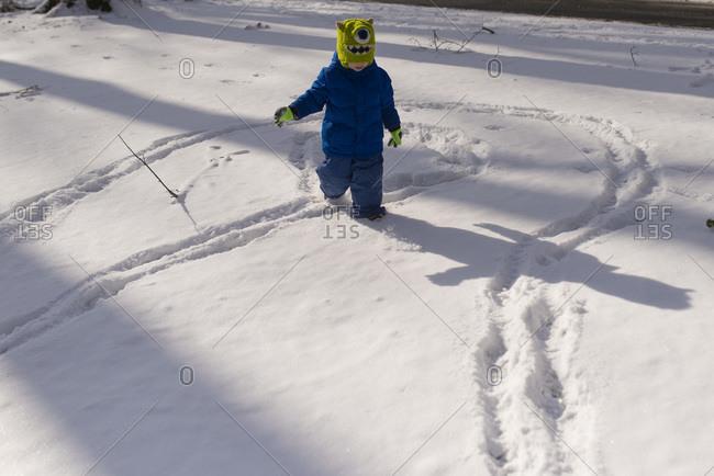 Boy in snowsuit making tracks in his backyard