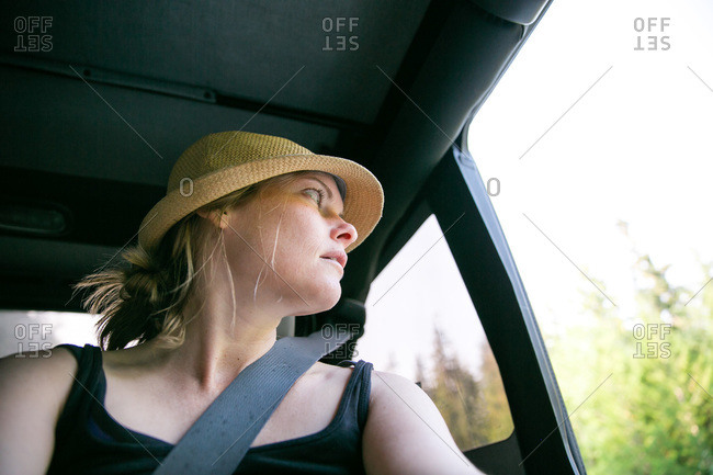 Young woman looking out of an open vehicle door