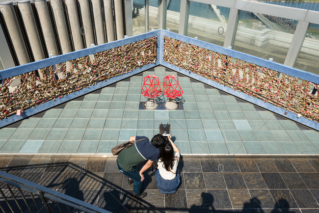Osaka-shi, Japan - September 22, 2015: Couple taking a photograph of locks on a railing at a modern Japanese skyscraper