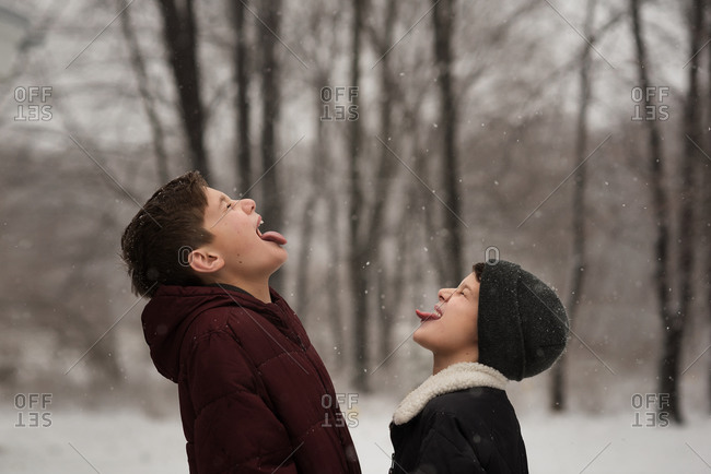 Brothers facing each other and catching snowflakes in their mouths