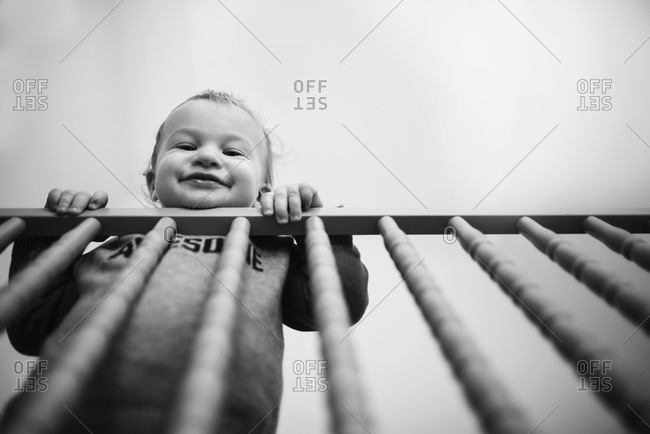 Little boy looking down from a railing and smiling