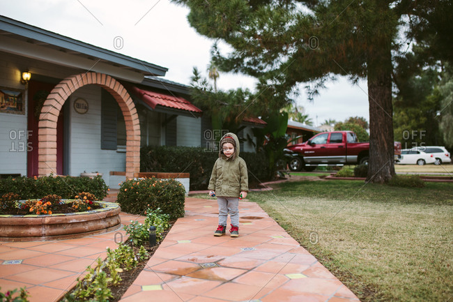 Child in hooded jacket standing on sidewalk outside house