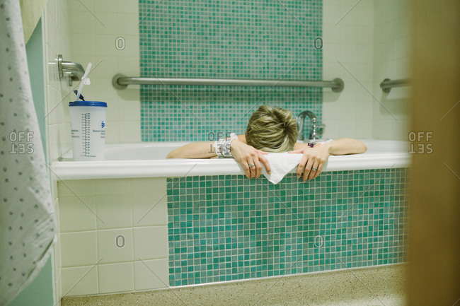 Woman in labor resting head on edge of birthing tub