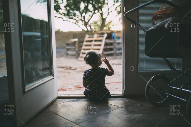 Toddler girl sitting in doorway of house