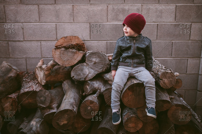 Little boy in knit hat and leather jacket sitting on wood pile