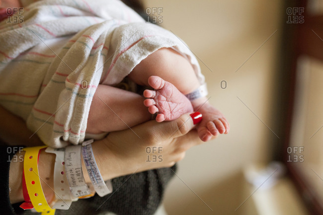 Close-up of new mother's hands holding her infant's feet in hospital