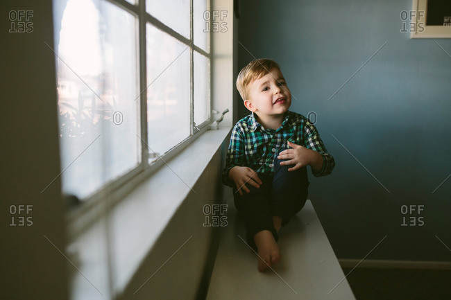 Young boy sitting on bench below a window
