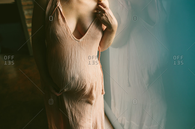 Pregnant woman in gauze dress standing against window