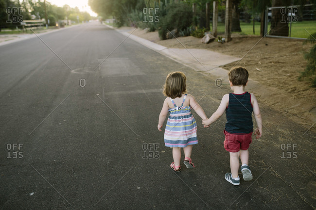 Toddler boy and girl walk hand-in-hand down street in small town