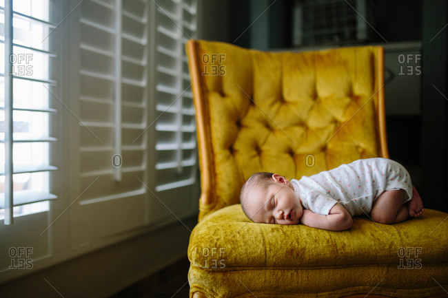 Sleeping baby on gold velour chair