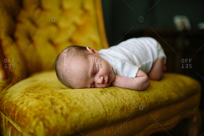 Close-up of sleeping baby on edge of gold velour chair
