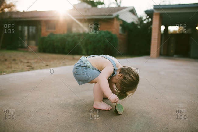 Toddler girl squatting to look through her legs in driveway