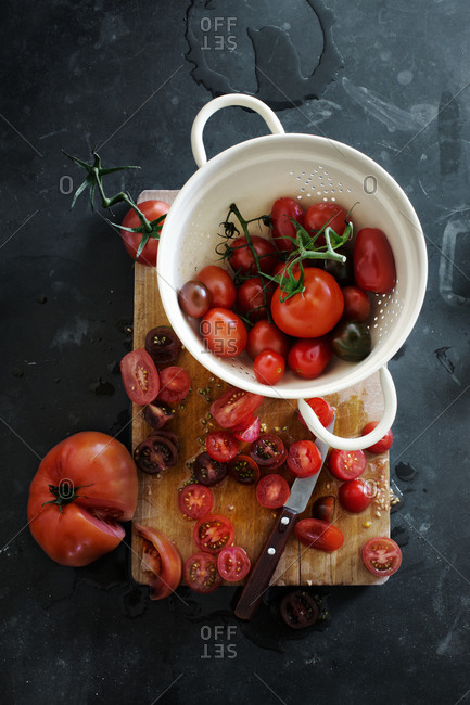 Variety of tomatoes in a colander on a cutting board