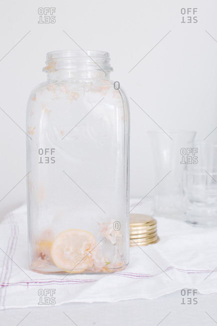 Remains of a lilac cordial beverage in a glass serving jar