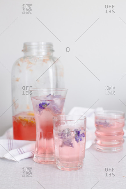 Glasses of a lilac cordial beverage with violet ice cubes