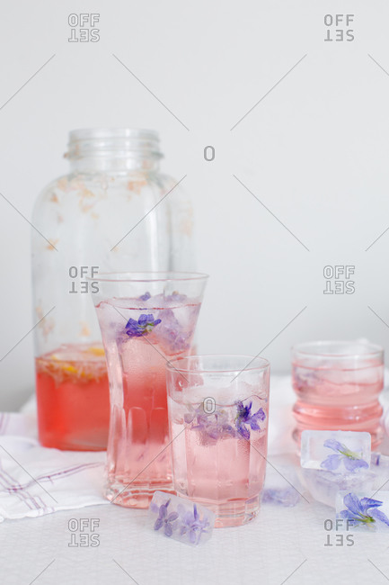 Glasses of a lilac cordial with violet-infused ice cubes