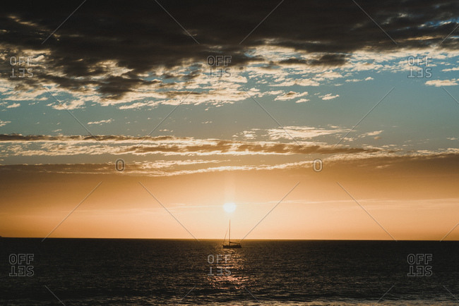 Silhouette of a sailboat directly under the sun at sunset