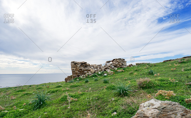 Crumbling stone foundation of house on hillside above the sea