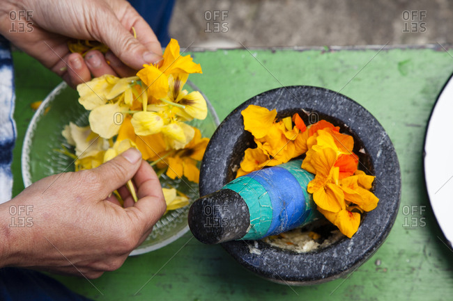 Woman putting yellow flower petals into bowl